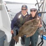 Ken Y. and Jen C. holding a california halibut on a CCFRP trip