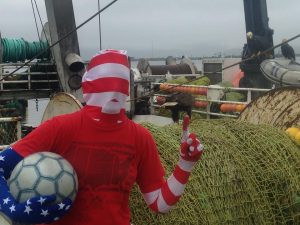 Jackie M. wearing patriotic clothes with a soccerball on a fishing boat