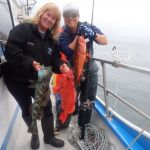 Volunteer angler and science crew member with lingcod, vermilion rockfish, and boccacio rockfish