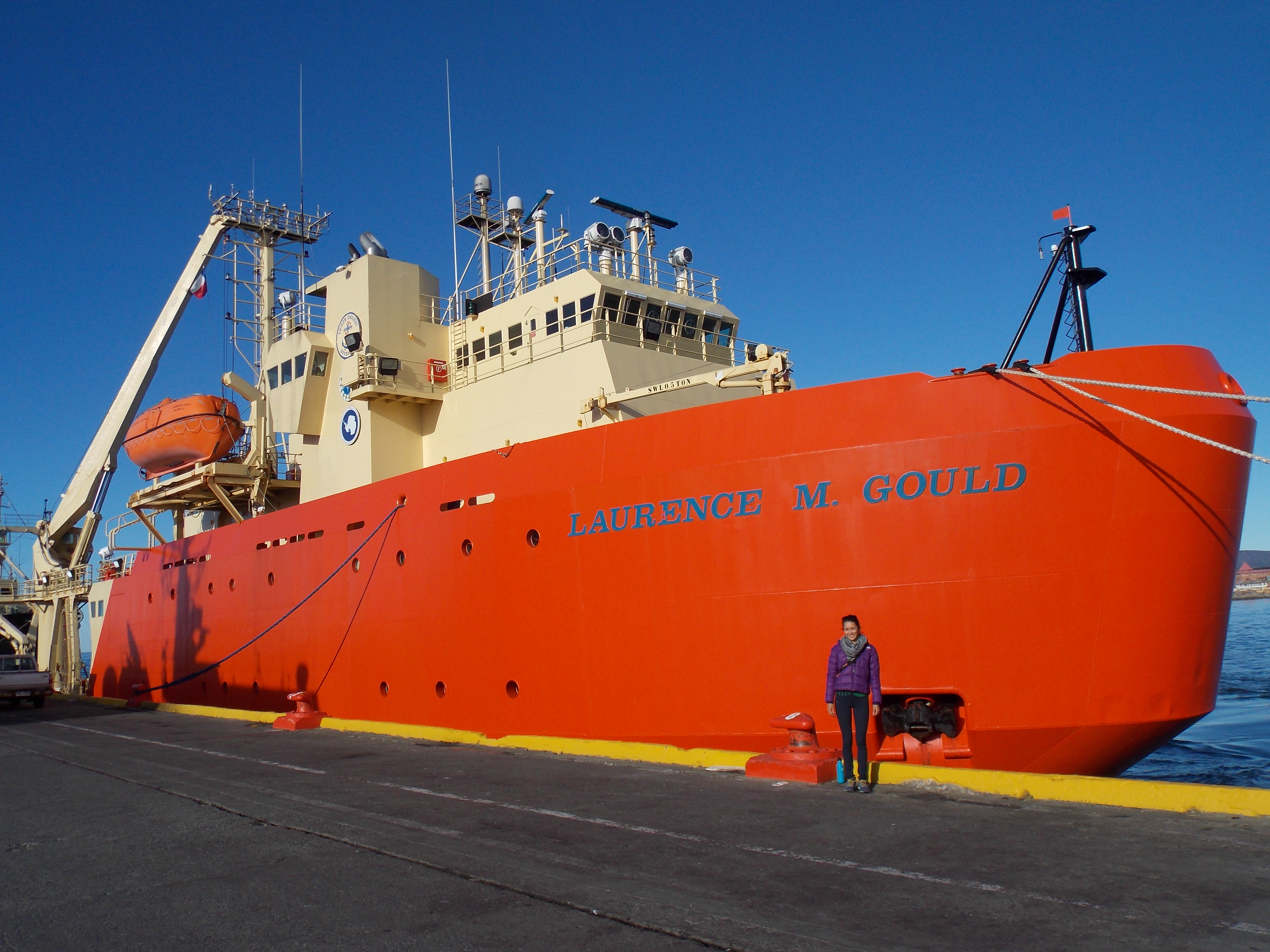 Jamie standing in front of the US's National Science Foundation's icebreaker and research vessel, the Laurence M. Gould, named after an American scientist.