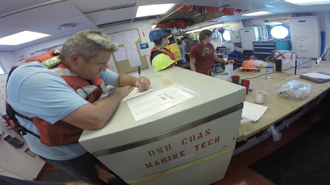 MPSL director Wes Heim helps prepare labels before mustering the science crew on deck.