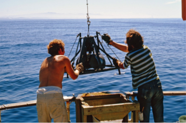 John Oliver & Al Hodgson lowering Smith-McIntyre grab to collect benthic samples for Sea Grant project.